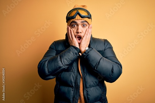 Photo Young brazilian skier man wearing snow sportswear and ski goggles over yellow ba