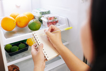 Woman Checking Refrigerator And Making Shopping List Before Going To Grocery Store