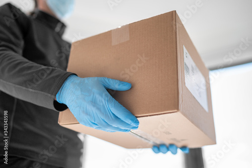 Foto Home delivery shopping box man wearing gloves and protective mask delivering packages at door