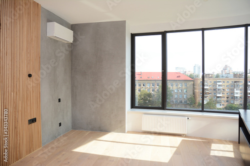 Fototapeta An empty apartment room with a large window and radiator heater, wood paneled and gray painted wall with air conditioner and wood laminated floor. obraz