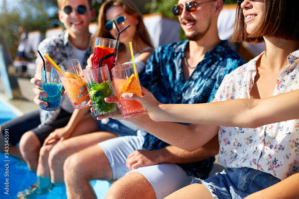 Fototapeta Close view. Friends clinking glasses with fresh colorful cocktails sitting by swimming pool on sunny summer day. People toast drinking beverages at luxury villa poolside party on tropical vacation.