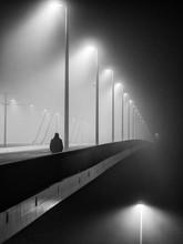 Rear View Of Man Walking On Illuminated Bridge At Night