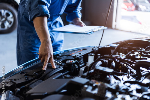 Foto Car mechanic holding clipboard and checking to maintenance vehicle by customer claim order in auto repair shop garage