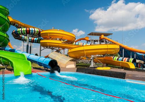 Fototapeta Water park with colorful slides and pools obraz na płótnie