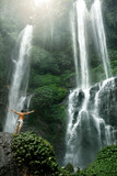 Freedom Of Life. Free Happy Healthy Man Enjoying Nature Beauty Raising Hands Up To Sky. Male Relaxing Near Beautiful Paradise Waterfall On Summer Travel Vacation. Enjoyment, Health, Wellness Concept