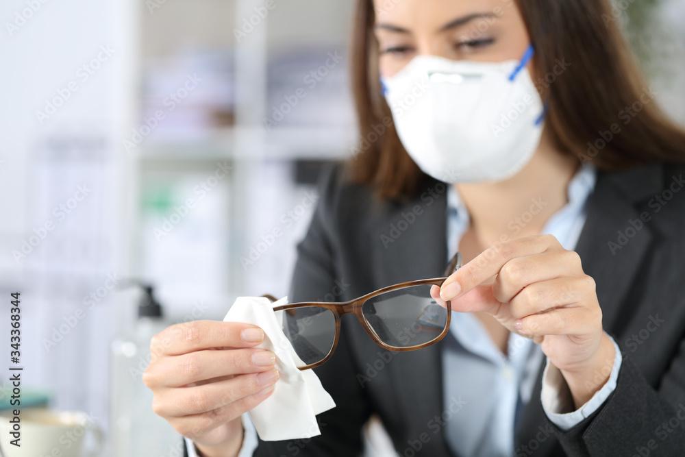 Fototapeta Executive wearing mask disinfecting glasses with sanitizer