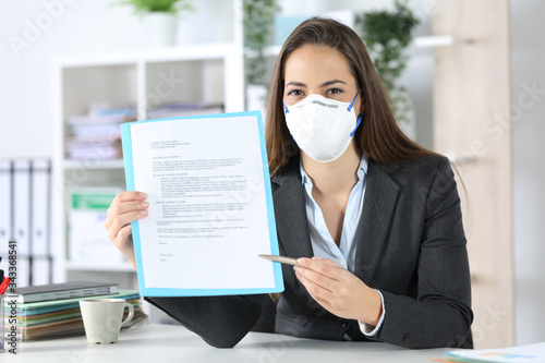 Executive with mask showing contract at camera at office Canvas Print