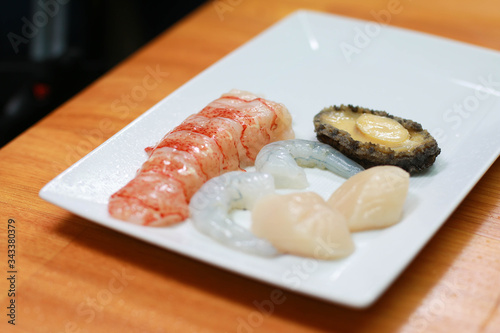 Photo Peeled lobster, shrimp, prawns and abalone on a wooden table