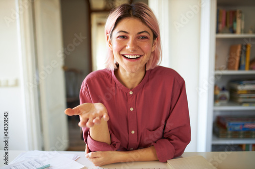 Obraz Happy cute teenage girl with pinkish hair smiling broadly while talking to friend online using video conference service. Stylish young female influencer recording vlog via webcam on electronic device - fototapety do salonu