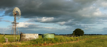 Panoramic Image Showing Long Stretching Green Farm Fields Under A Cloudy Sky With A Wind Powered Water Pump And Cement Tank In The Foreground, Hamilton, Rural Victoria, Australia