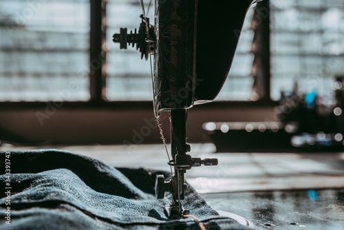 Fototapeta Closeup the sewing machine and item on denim jeans, old sewing machine. obraz