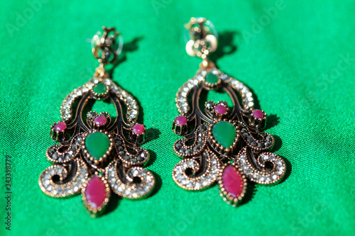 Fotografija earrings inlaid with semi-precious stones at green background