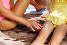 Closeup, Female Hand Draws Heart Of Sunscreen Creamy Foot Of Baby.