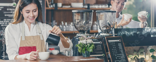 Fototapeta Banner of Asian Barista preparing cup of coffee, espresso with latte or cappuccino for customer order in coffee shop,bartender pouring milk,Small business owner and startup in coffee shop concept obraz