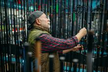 Male Angler Choosing Rod In Fishing Shop