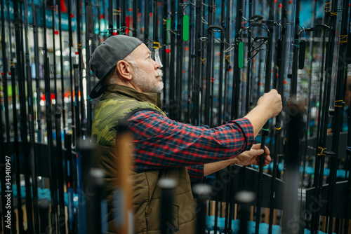 Male angler choosing rod in fishing shop Wallpaper Mural