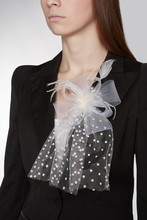 Cropped Shot Of A Brown-haired Lady In A White Top Under A Black Jacket With A White Veil Broach. The Fancy Breastpin Is Made As A Mesh Bow With Polka-dot Pattern And Decorated With Feathers.