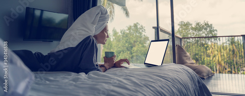 Photo Young beautiful young woman in a white shirt sits on a white bed in a hotel room