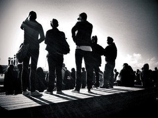 Rear View Of A Group Of People Against The Sky