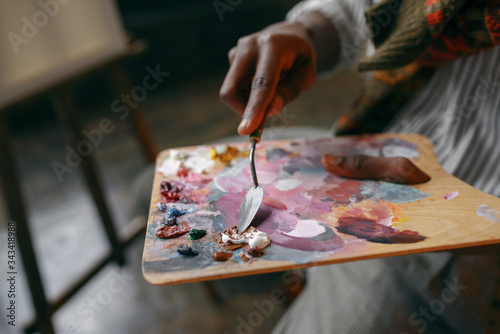 Photo Painter holds brush and colorful paints on palette