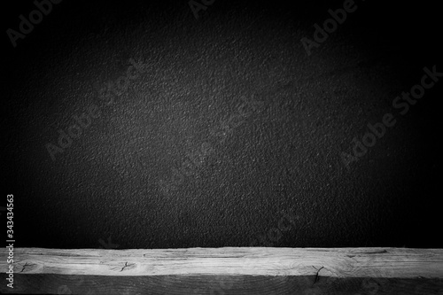 Photo Old wooden table top with a dirty concrete block wall in a dark room background