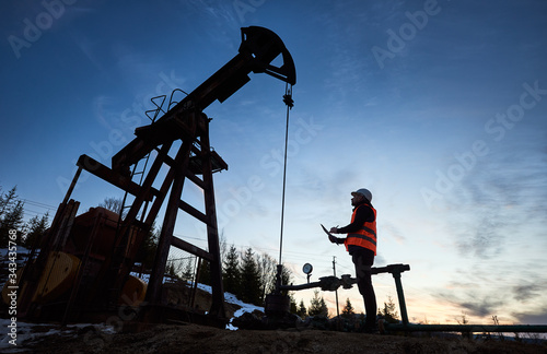 Side view snapshot of an oil engineer wearing orange vest and a helmet, looking at the oil rig and making some notes against beautiful evening sky. Concept of oil extraction and petroleum industry.