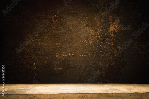Old wooden table top with a dirty concrete block wall in a dark room background Canvas Print