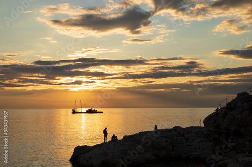 Rovinj Coast Rocks and Boat Silhouette at Sunset