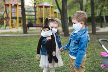 Child Boy And Girl Walking Outdoors With Face Mask Protection. Little Girl Holds A Stuffed Monkey In Her Hands. Coronavirus, Covid-19