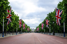 Empty Road Amidst British Flags Against Cloudy Sky
