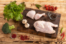 Raw Chicken And Vegetables On A Wooden Cutting Board
