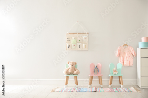 Cute toys on chairs with bunny ears near white wall indoors, space for text. Children's room interior