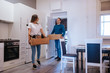 An attractive caucasian man and woman are entering a new apartment with boxes of things. A loving couple moves in