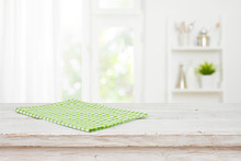 Green Kitchen Towel On Wooden Table Over Blurred Window Background