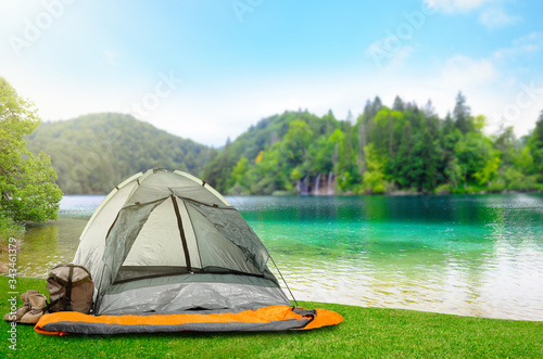 Camping tent with sleeping bag and boots near beautiful river Canvas