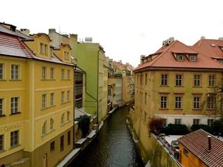 Fototapeta na wymiar Canal Amidst Houses Against Clear Sky