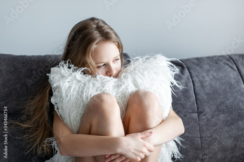 Depression in adolescence - a young blonde girl sitting on a sofa, hugs a pillow Canvas Print