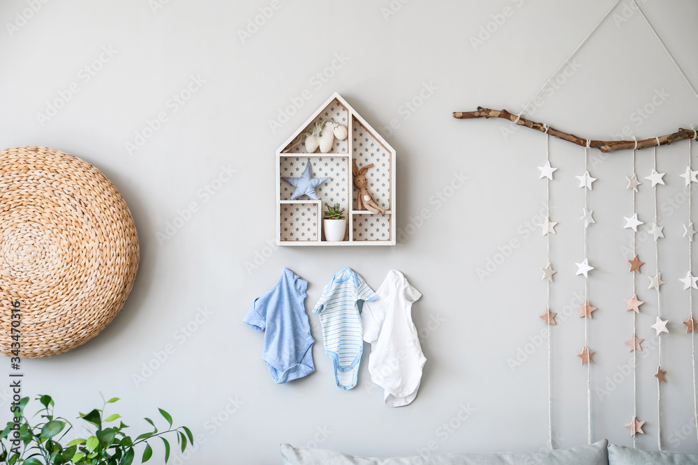 Fototapeta Stylish shelf with toys and clothes hanging on wall in children's room