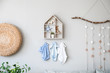 Stylish shelf with toys and clothes hanging on wall in children's room
