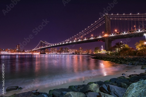 Valokuvatapetti Illuminated Manhattan Bridge Over East River Against Clear Sky At Night