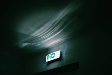 Low Angle View Of Illuminated Exit Sign In Restroom