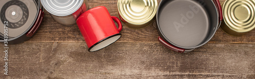 Obraz panoramic shot of tin cans, metal dishes and cup on wooden table - fototapety do salonu