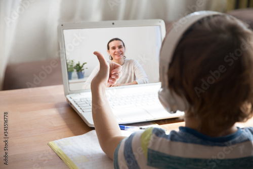 child boy  in headphones  show sight thumbs up, is using a laptop and Communicates with the teacher online  at home Wallpaper Mural