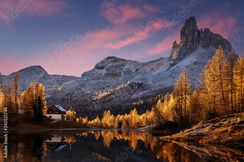 Wall mural - Wonderful autumn landscape during sunset. Fairy tale moutain lake with picturesque sky, majestic rocky mount and colorful trees glowing sunlight. Amazing nature scenery. Federa lake. Dolomites Alps.