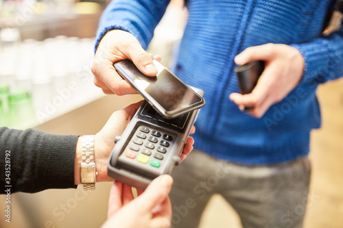 Fotomural Customer pays contactless with smartphone via NFC