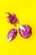 canvas print picture - Red cabbage - cut head and sliced - on yellow desk from above