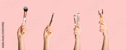 Obraz na plátně Various makeup brushes in female hands on pink background, closeup
