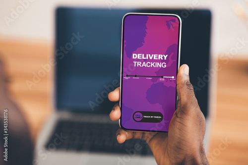 Fototapeta Close-up of african man holding mobile phone with app on screen obraz
