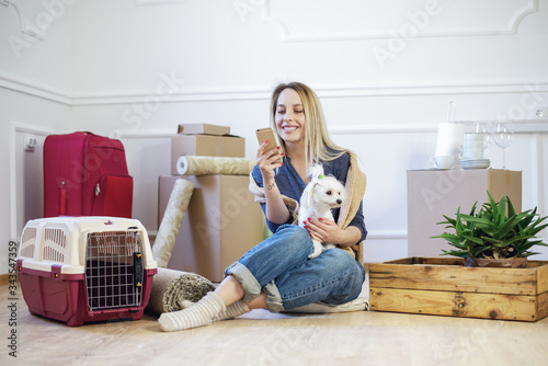 Photo Home sweet home! A young girl in casual attire sits cross-legged on the floor of