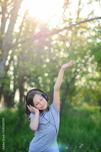 Young girl is dancing and listening the music till walking in the park Wallpaper Mural